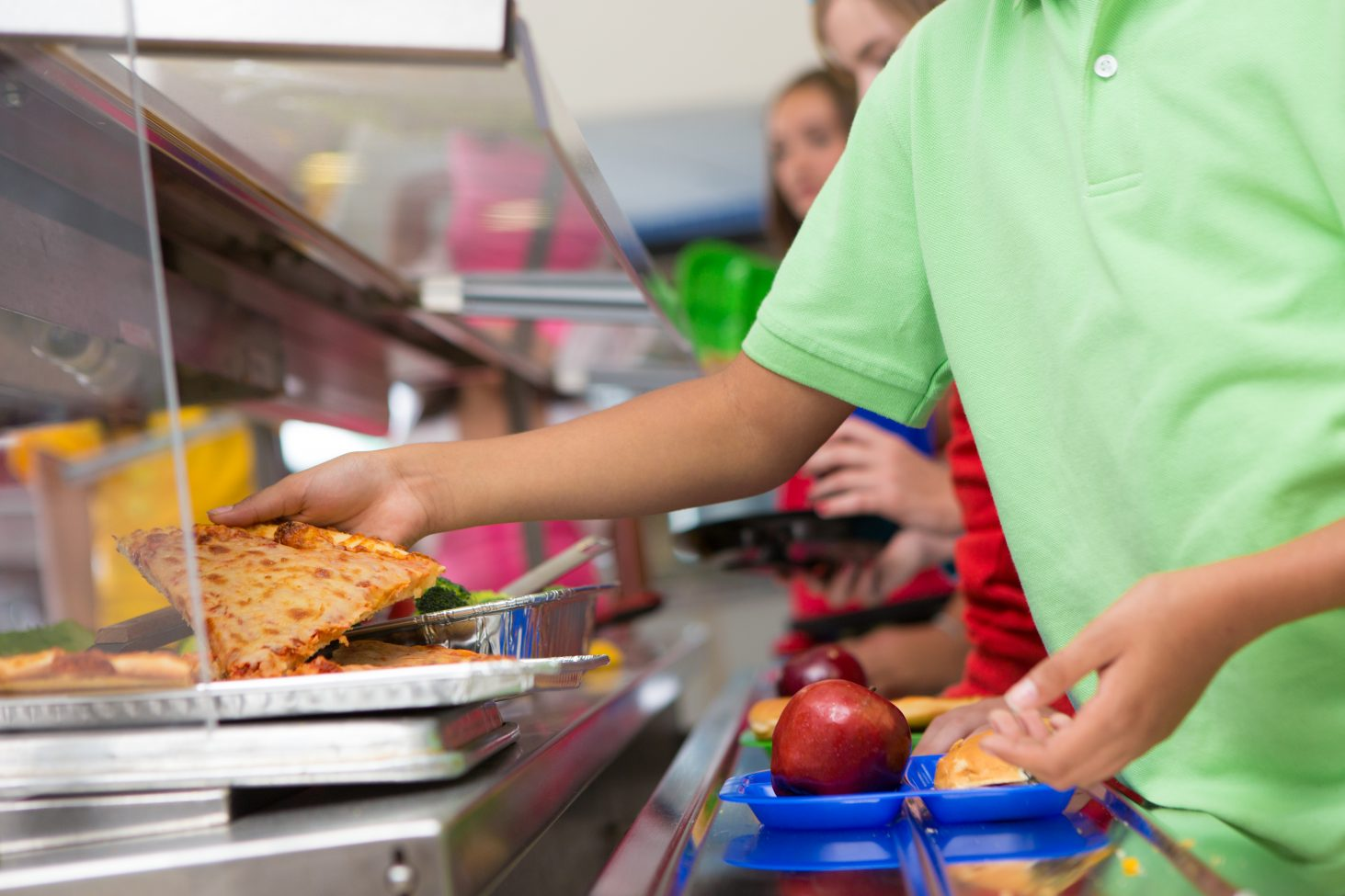 Boy choosing piece of pizza in the school lunch line